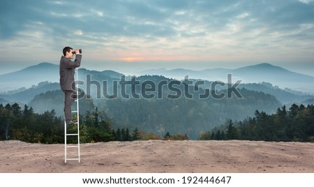 Businessman standing on ladder against scenic countryside with mountains - stock photo