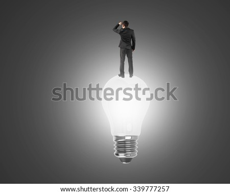 Businessman standing on light bulb with bright white light, on black background. - stock photo