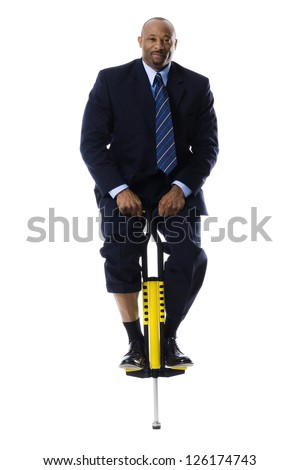Businessman standing on pogo stick - stock photo