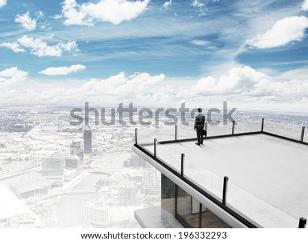 businessman standing on roof of skyscrapper - stock photo