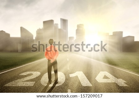 Businessman standing on the road of 2014 while looking at the future - stock photo