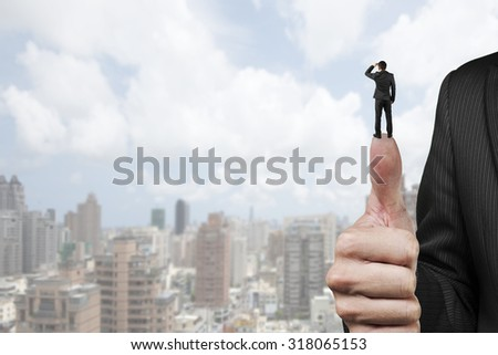 Businessman standing on top of another big thumb, with cloudy sky cityscape background. - stock photo