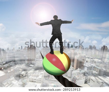 Businessman standing on top of colorful ball, balancing on a wire, with sun mist cityscape background. - stock photo