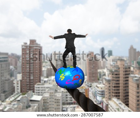 Businessman standing on top of colorful symbols ball, balancing on a wire, with cityscape background. - stock photo