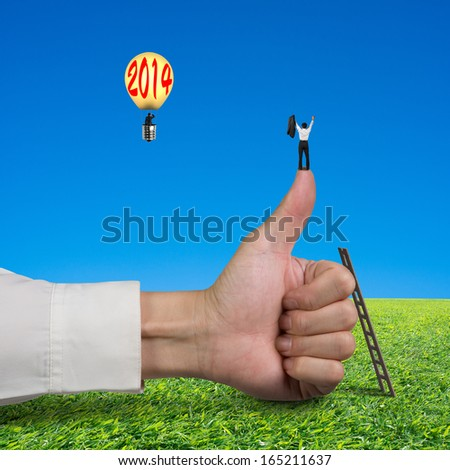 Businessman standing on top of thumb, another in lamp balloon with 2014, meadow and blue sky background - stock photo