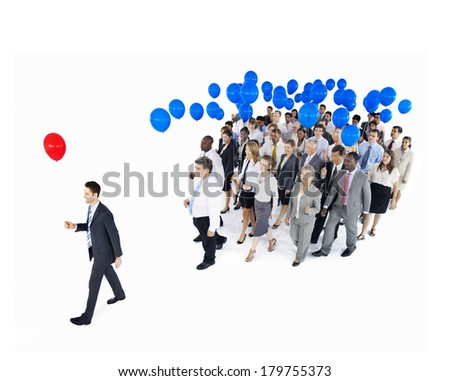 Businessman Standing Out From Crowd with Red and Blue Balloons - stock photo
