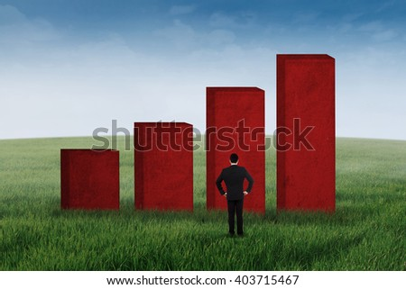 Businessman standing outdoors looking at a business graph - stock photo
