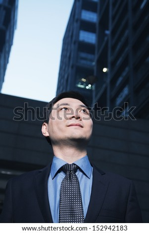 Businessman standing outdoors, low angle view, Beijing - stock photo