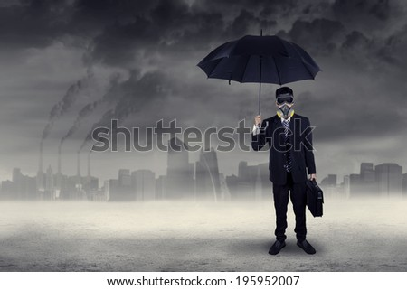 Businessman standing outdoors wearing a gas mask while holding an umbrella and briefcase - stock photo