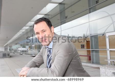Businessman standing outside congress center - stock photo