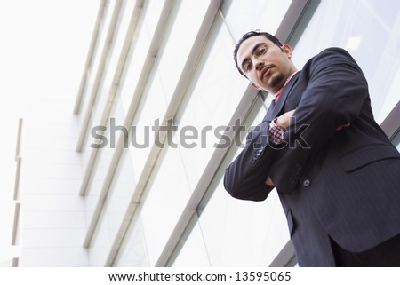 Businessman standing outside office block looking to camera - stock photo