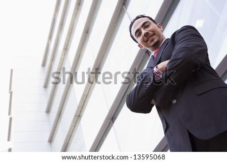Businessman standing outside office building looking to camera - stock photo