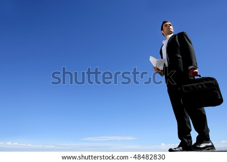 Businessman standing outside with blue sky - stock photo