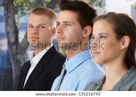 Businessman standing outside with colleagues, looking at camera confidently. - stock photo