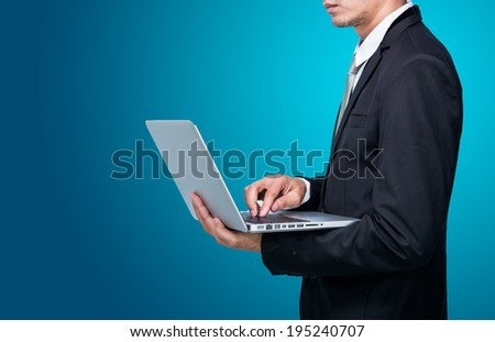 Businessman standing posture hand hold notebook laptop isolated on blue background - stock photo