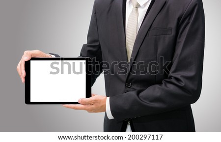 Businessman standing posture hand holding blank tablet isolated on over gray background - stock photo