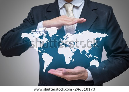 Businessman standing posture hand holding world map isolated on gray background - stock photo