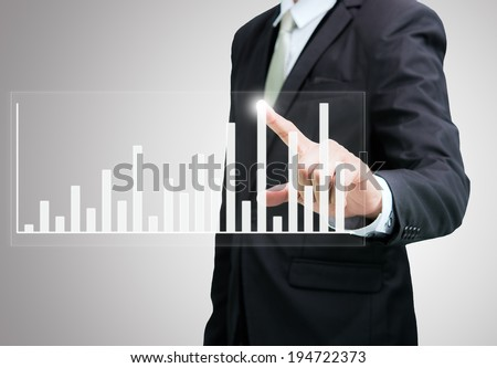 Businessman standing posture hand touch graph finance isolated on over gray background - stock photo