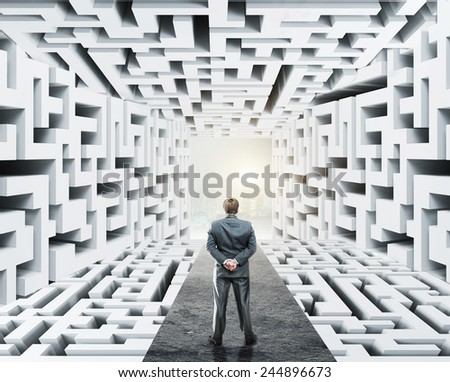 Businessman standing surrounded by labyrinth - stock photo