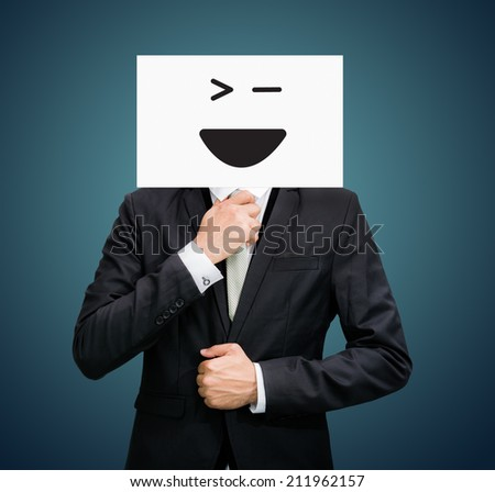 Businessman standing white paper happy smile face holding front of head on dark background - stock photo
