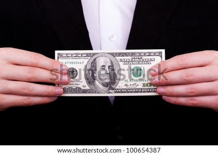 Businessman standing with a hundred american dollars in his hand - stock photo