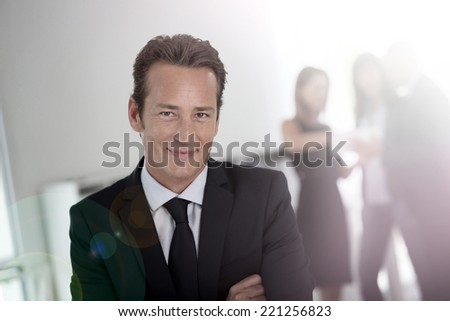 Businessman standing with arms crossed, people in background - stock photo