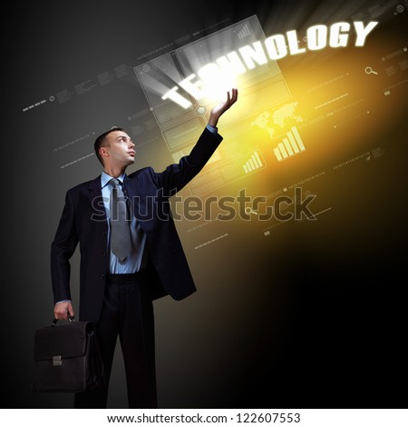 Businessman standing with modern technology symbols next to him - stock photo