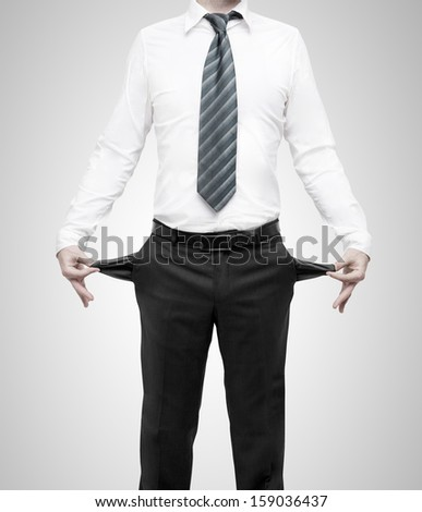 businessman standing with pockets turned inside out - stock photo