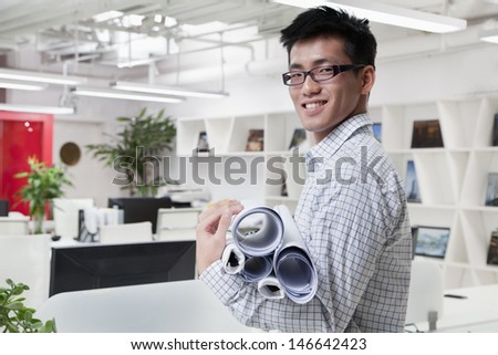 Businessman standing with stuck of papers in the office, portrait - stock photo