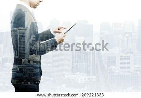 businessman standing with tablet double exposure - stock photo