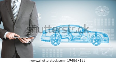 Businessman standing with tablet pc . On background of the high-tech wire frame car and graphs - stock photo