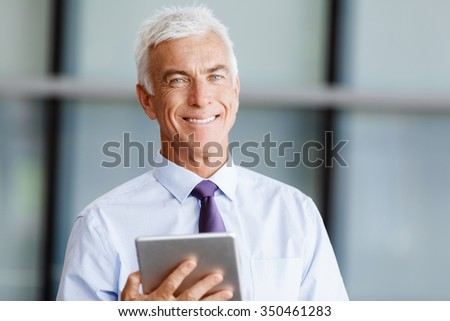 Businessman standing with tablet smiling at camera - stock photo