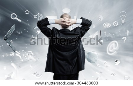 Businessman stands back and looks at flying objects - stock photo