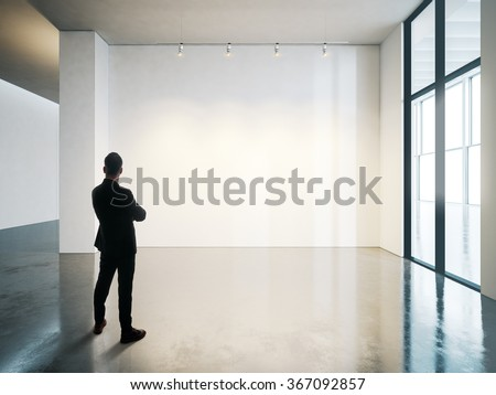 Businessman stands in blank white museum interior with concrete floor. Horizontal - stock photo