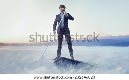 Businessman steering on clouds to improve his career - stock photo