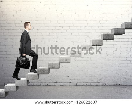 Businessman stepping up a career stair - stock photo