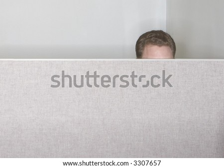 Businessman sticks up the top of his head just above the cubicle in the office so you can only see his hair and forehead - stock photo