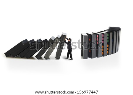 Businessman stopping the domino effect, Concept for solution to a problem by stopping the domino effect - stock photo
