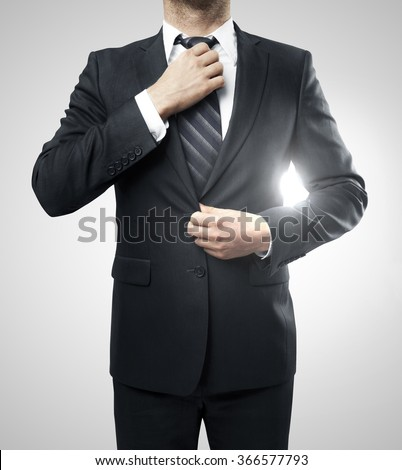 Businessman straightens his tie on a white background - stock photo