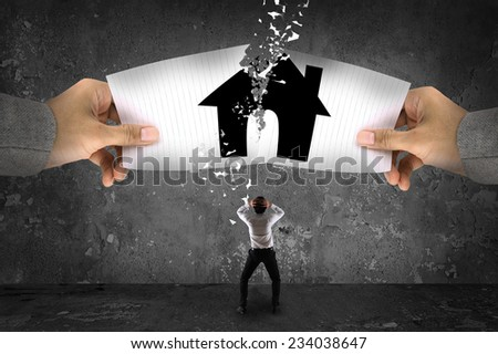 Businessman stress, ripping up a house on paper - stock photo
