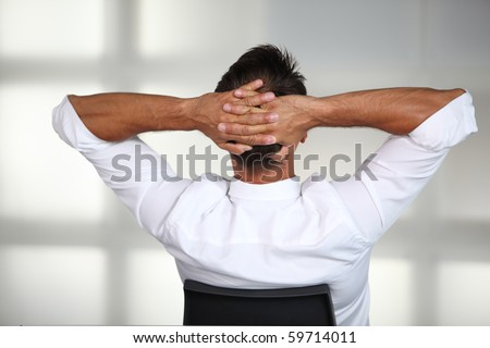 Businessman stretching arms in the office - stock photo