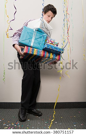 Businessman struggling with pile of presents - stock photo