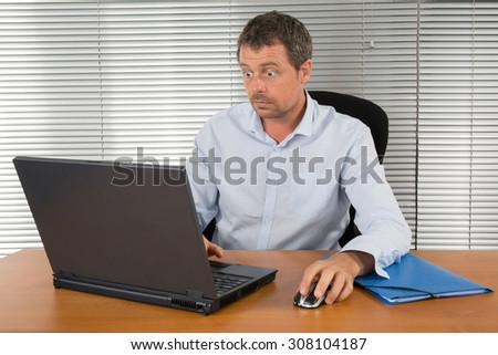Businessman stunned and amazed staring at his laptop - stock photo
