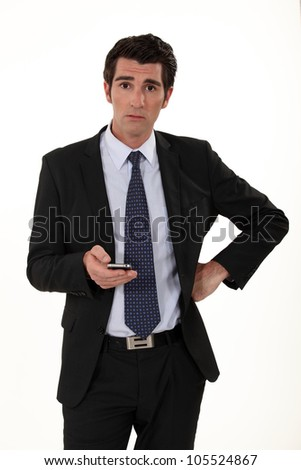 Businessman surprised by text message - stock photo