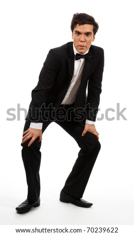 Businessman take a respite from competition, standing with his hands on knees, isolated on white and looking at camera - stock photo