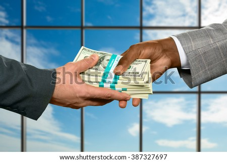 Businessman takes big money. Office employee gives huge cash. More than grateful. This day has just started. - stock photo