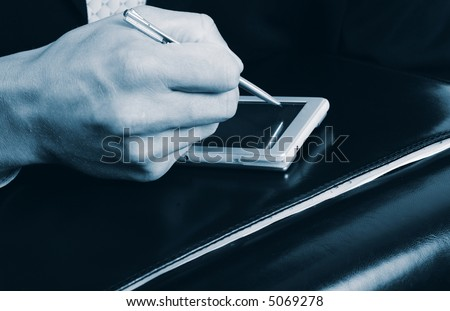 Businessman taking notes on PDA - stock photo