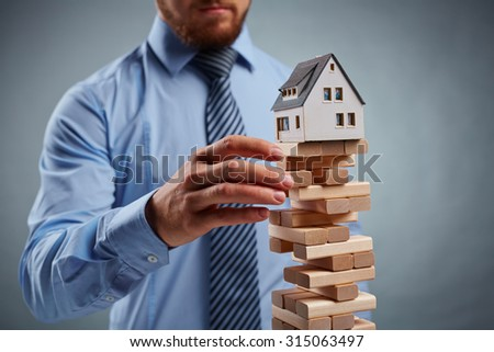 Businessman taking out wooden block from tower with house model on its top - stock photo