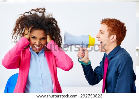 businessman talking in megaphone to african executive with scared expression - stock photo