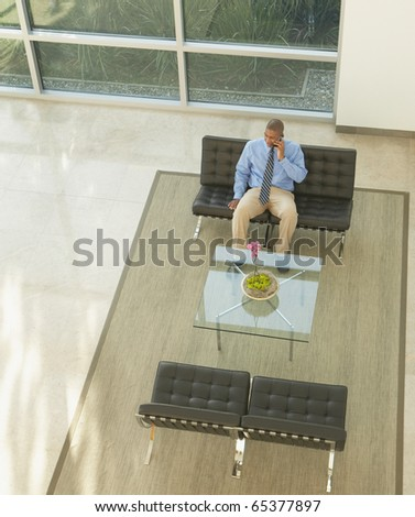 Businessman talking on a cell phone in lobby area - stock photo